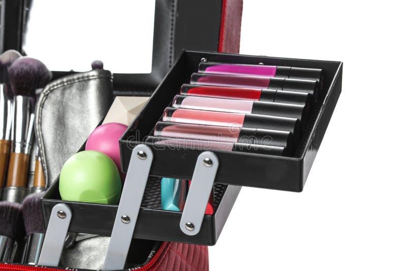 Stilfullt fall med makeupprodukter och skönhettillbehör på vit bakgrund arkivfoto