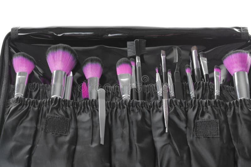 Stilfullt fall med pincett och borstar för att applicera makeupprodukter på vit bakgrund royaltyfria foton