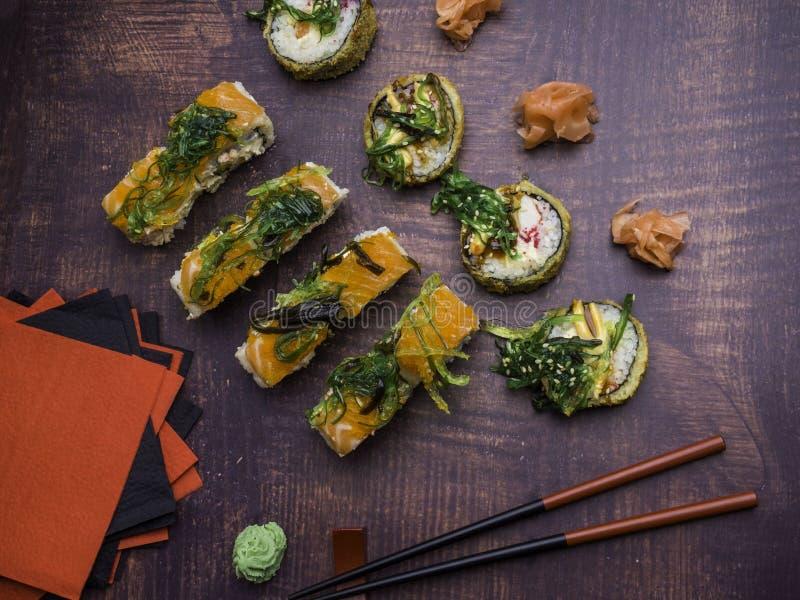 Stilfullt japanskt mål över mörk brädevariation av sushirullar med laxen, räka, krabban, wakame och avokadot, wasabi, ingefära royaltyfria bilder