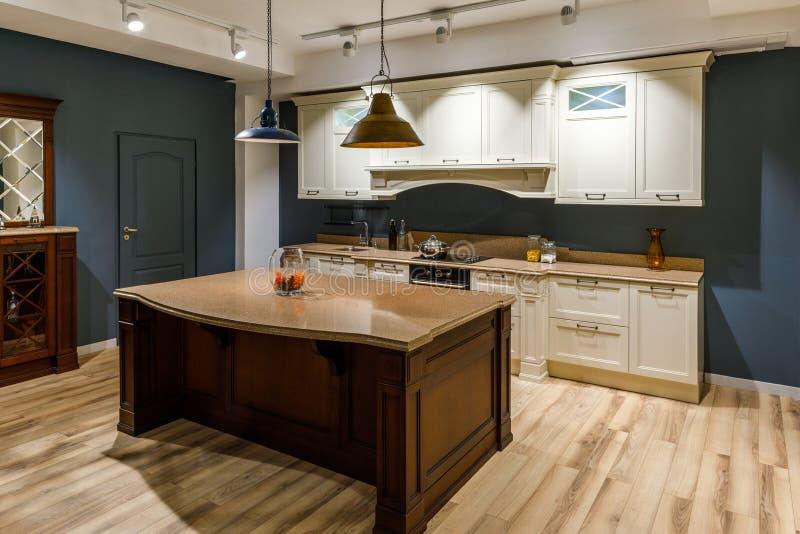 Stilfullt kök med den eleganta träräknaren och vita kabinetter royaltyfri foto