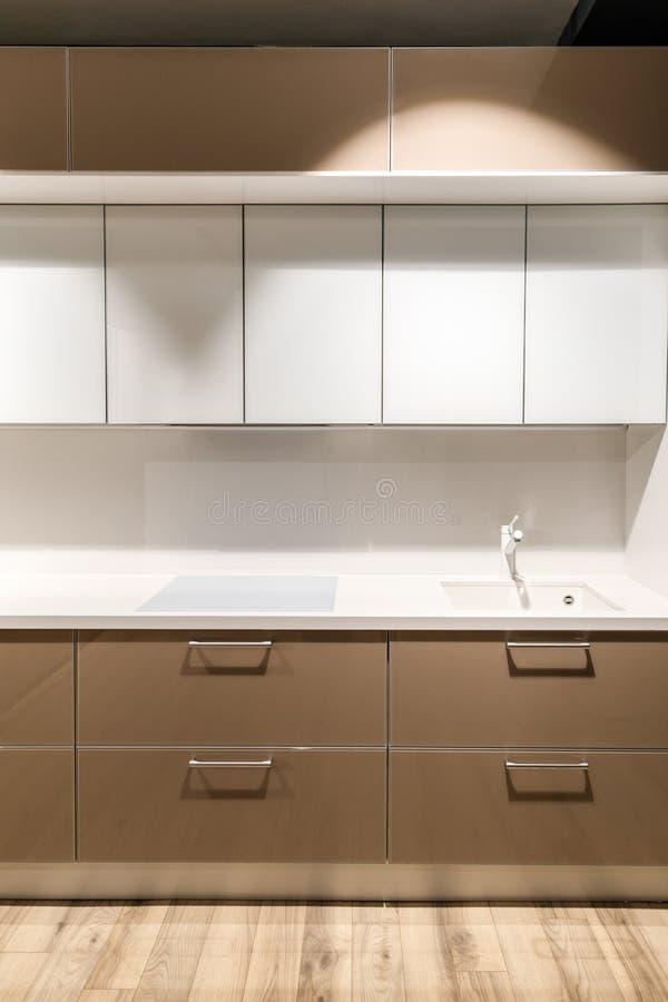 Stilfullt kök med elegant vit och brunt kontrar arkivfoton