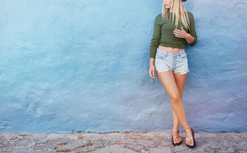 Stilfullt kvinnligt modellanseende mot den blåa väggen royaltyfria bilder