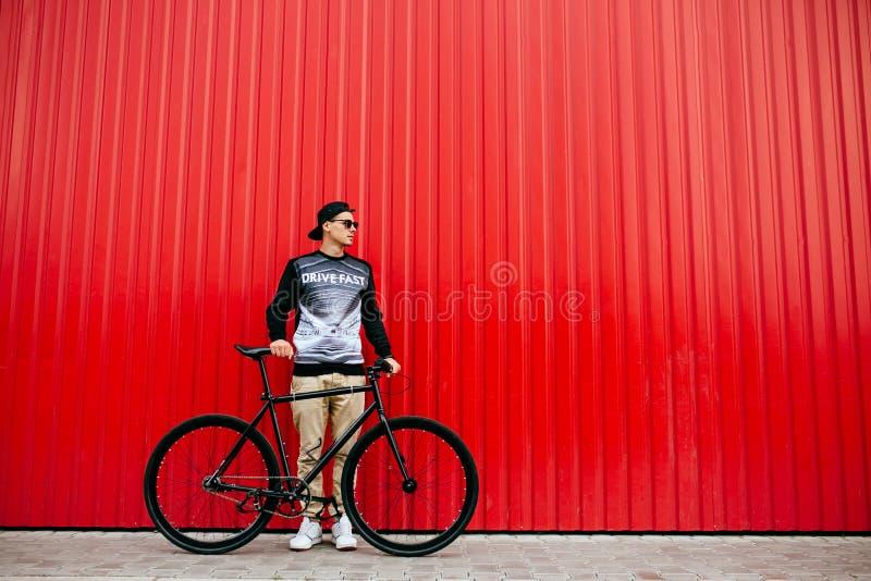 Stilfullt mananseende med cykeln mot den stads- röda väggen arkivfoton