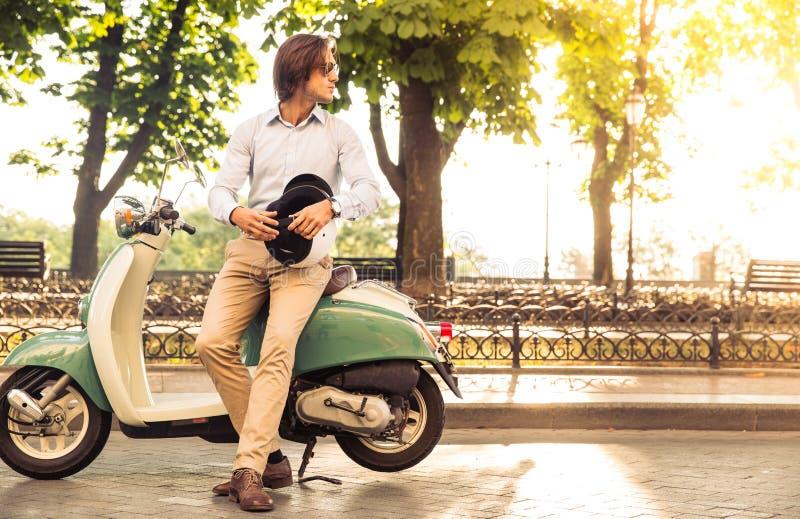 Stilfullt mananseende nära hans sparkcykel med hjälmen arkivbild