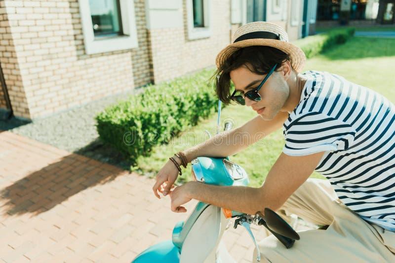 Stilfullt mansammanträde på den retro sparkcykeln royaltyfri fotografi