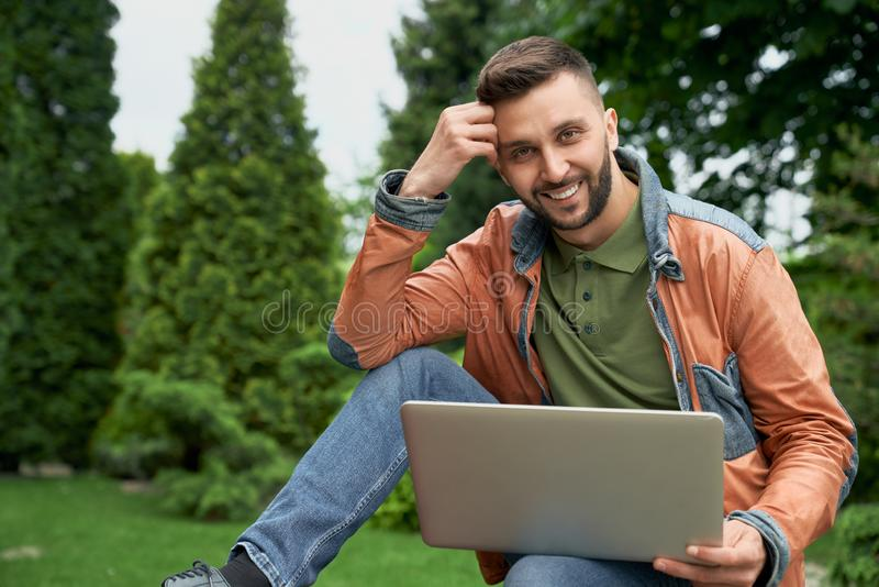 Stilfullt posera för man som sitter med bärbara datorn i trädgård arkivbild