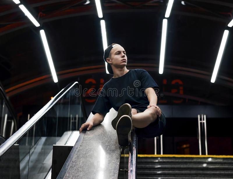 Stilfullt sammanträde för ung man på en rulltrappa royaltyfri foto