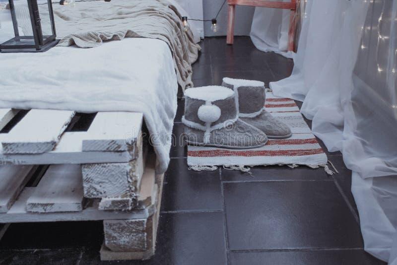 Stilfullt sovrum i gråa signaler, varma kängor på det mattt nära sängen av paletter arkivbild