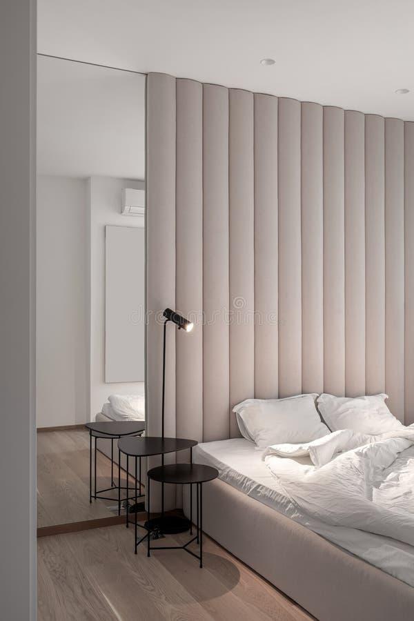 Stilfullt sovrum i modern stil med den bruna textilväggpanelen fotografering för bildbyråer
