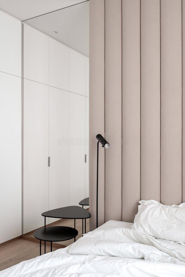 Stilfullt sovrum i modern stil med den bruna textilväggpanelen royaltyfri bild