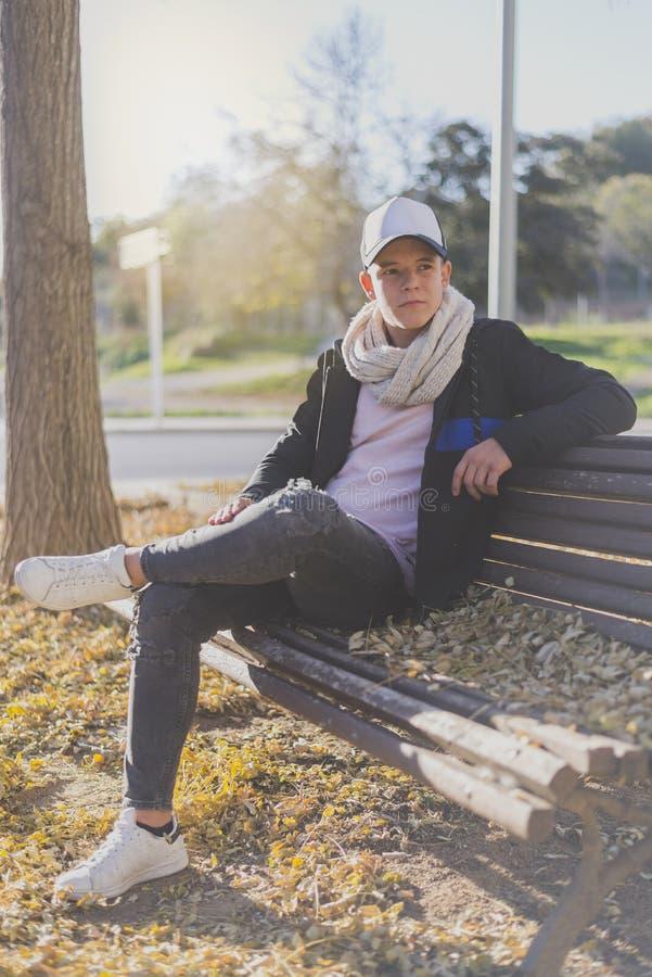 Stilfullt tonåringsammanträde på en träbänk på en stadsgatacasu fotografering för bildbyråer