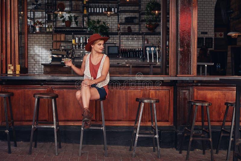 Stilfullt ungt kvinnligt sammanträde på ett kafé med drinken royaltyfri bild