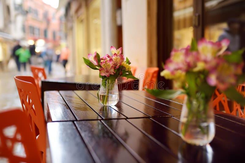 Stilfullt utomhus- kafé i en liten europeisk stad royaltyfri foto