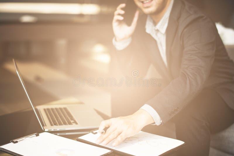Stilig affärsman i dräkt och glasögon som i regeringsställning talar på telefonen, skott för sidosikt av händer för man` ett s ge royaltyfria bilder