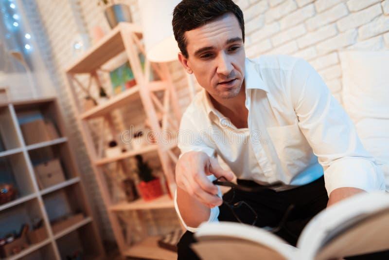 Stilig affärsman läst boksammanträde i säng Den vuxna mannen tog av hans läs- exponeringsglas, därför att hans ögon var trötta royaltyfria bilder