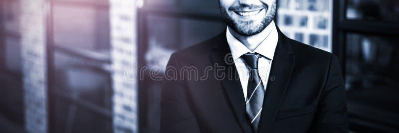 Stilig affärsman med armar korsat anseende i regeringsställning royaltyfria foton