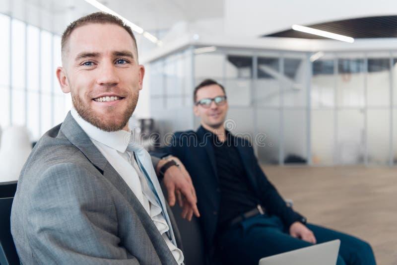 Stilig affärsman med kollegan på bakgrund på flygplatsen royaltyfri foto