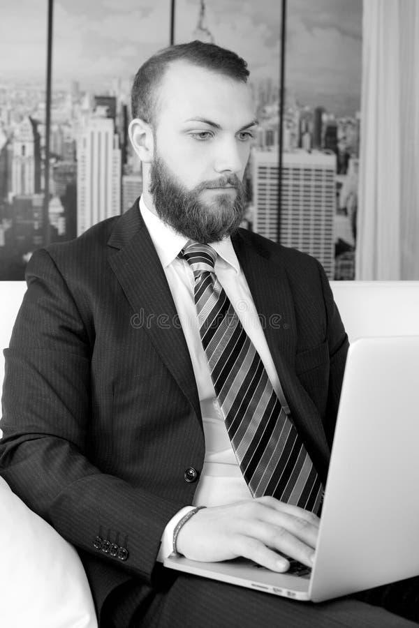Stilig affärsman med skägget som i regeringsställning arbetar på den svartvita bärbara datorn royaltyfri bild