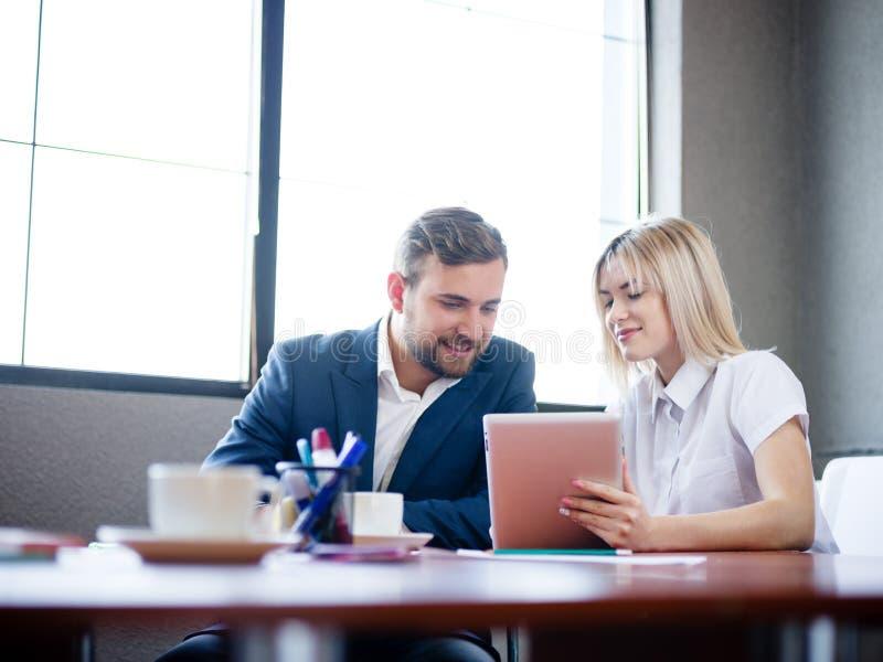 Stilig affärsman och kvinna som arbetar med minnestavlan på en suddig bakgrund Kontorsmötebegrepp kopiera avstånd arkivfoton