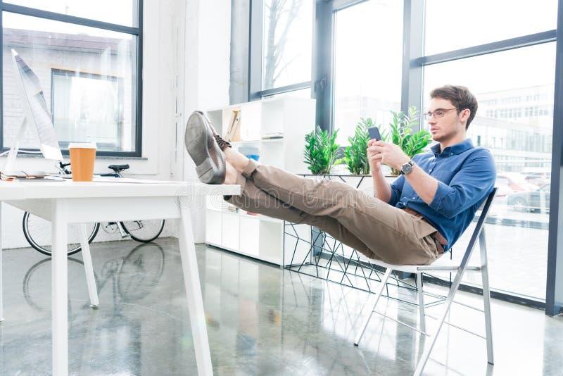 stilig affärsman som använder smartphonen, medan sitta fotografering för bildbyråer