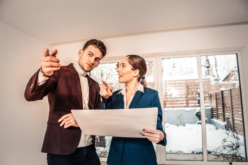 Stilig affärsman som frågar frågor till den yrkesmässiga fastighetsmäklaren arkivfoton