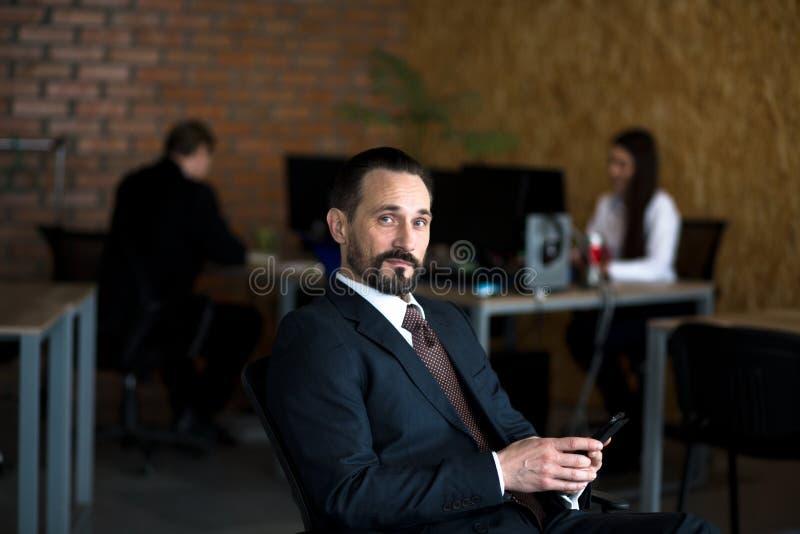 Stilig affärsman som framme sitter på hans stol av hans kontor Två kollegor arbetar bak honom royaltyfria bilder