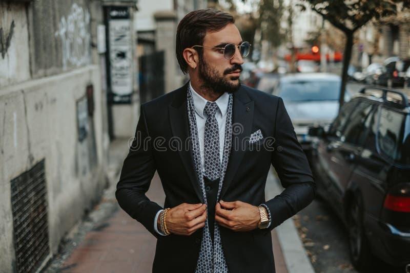 Stilig affärsman som går på trottoaren och knäppas jacke royaltyfria foton