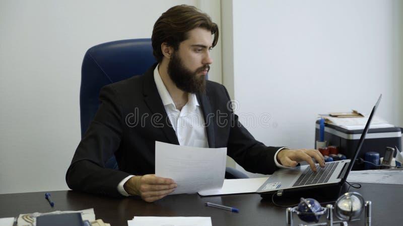 Stilig affärsman som i regeringsställning arbetar med bärbara datorn Ung affärsman med ett skägg som arbetar på datoren i kontore fotografering för bildbyråer