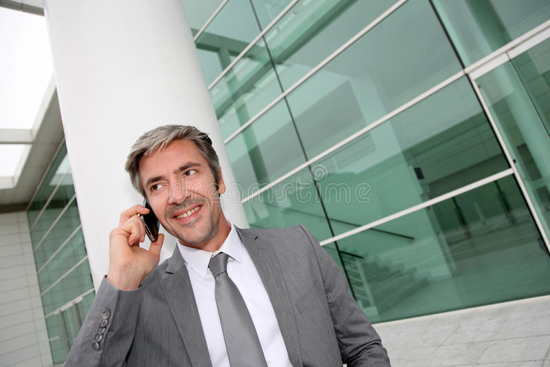 Stilig affärsman som ler och talar på telefonen arkivbilder