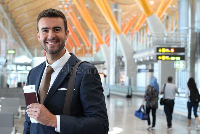 Stilig affärsman som ler på flygplatsen med utrymme för kopia arkivbilder