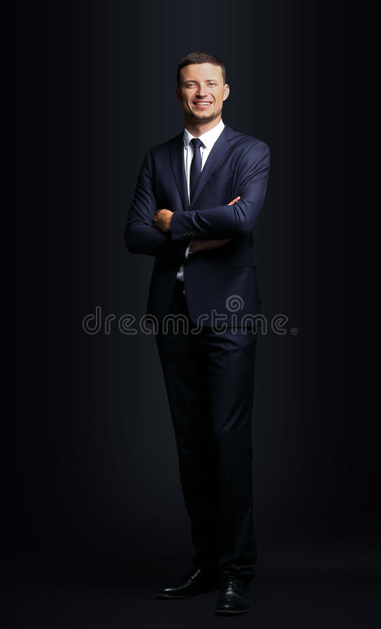 Stilig affärsman som ler på svart bakgrund arkivfoto