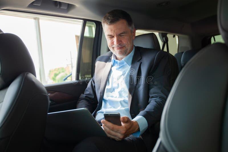 Stilig affärsman som talar med telefonsammanträde med bärbara datorn på backseaten av bilen royaltyfri foto