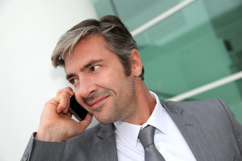 Stilig affärsman som talar på telefonen arkivfoton