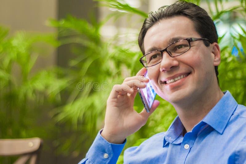 Stilig affärsman som talar på telefonen i ett kafé ung lyckad affärsman i en skjorta och ett band som talar på telefonen i en caf royaltyfria foton