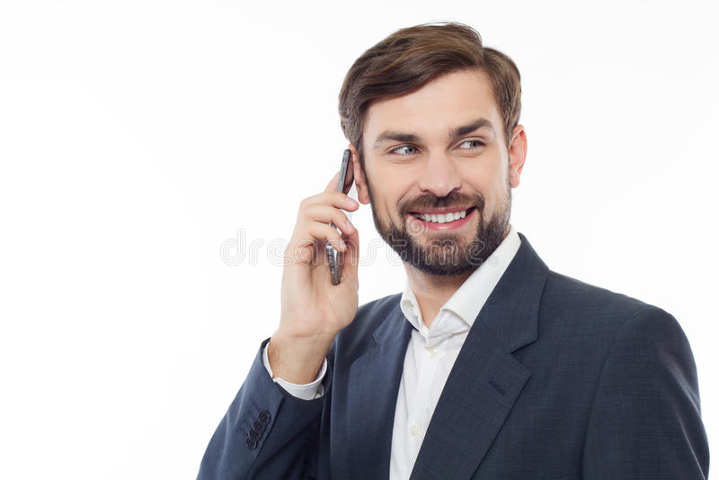 Stilig affärsman som talar på telefonen och ler, isolerat royaltyfri foto