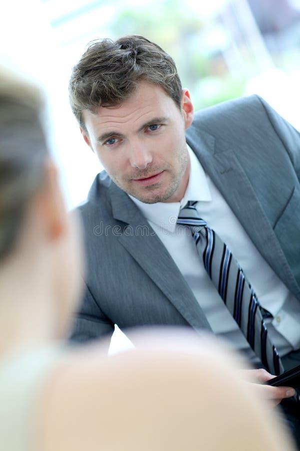 Stilig affärsman som talar till partnern arkivbild