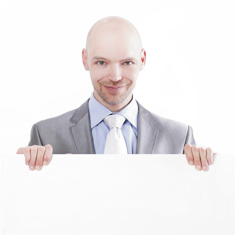 Stilig affärsman som visar det tomma plakatet Isolerat på vit arkivfoton