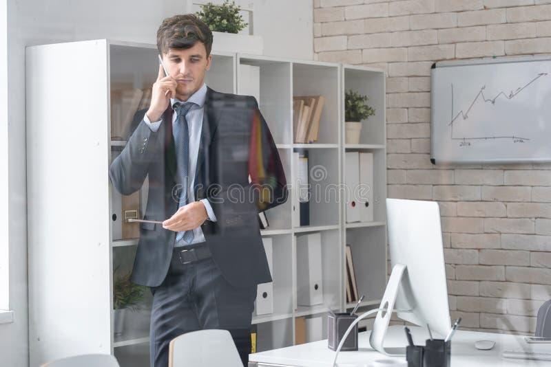 Stilig affärsman Speaking av telefonen som står n-kontoret royaltyfria bilder