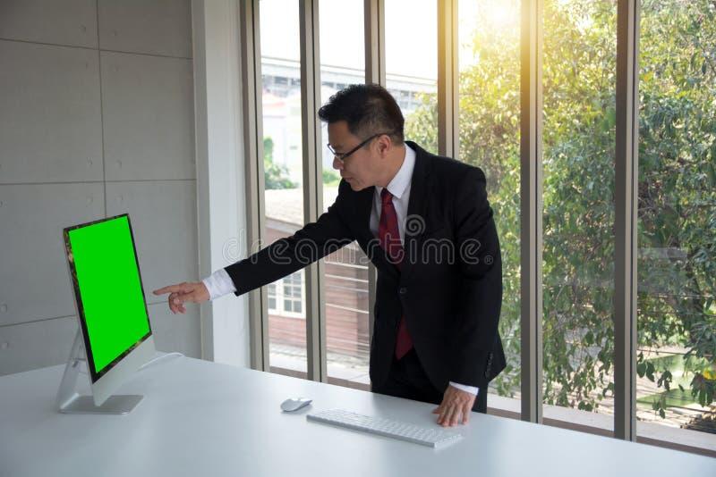 Stilig affärsmanpunkt fingret på en dator för tom skärm på tabellen med tangentbordet och musen arkivbilder