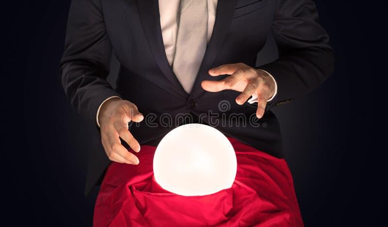 Stilig aff?rsman med den magiska bollen och m?rk tom bakgrund arkivbilder