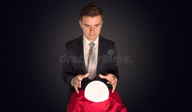 Stilig aff?rsman med den magiska bollen och m?rk tom bakgrund arkivfoto