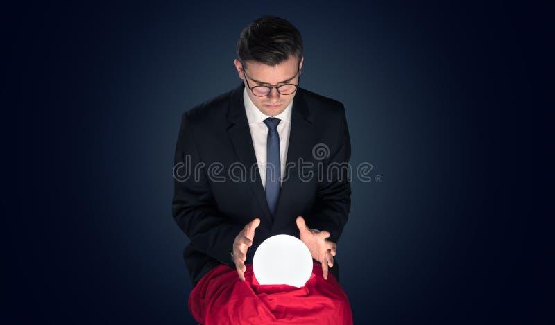 Stilig aff?rsman med den magiska bollen och m?rk tom bakgrund royaltyfria bilder