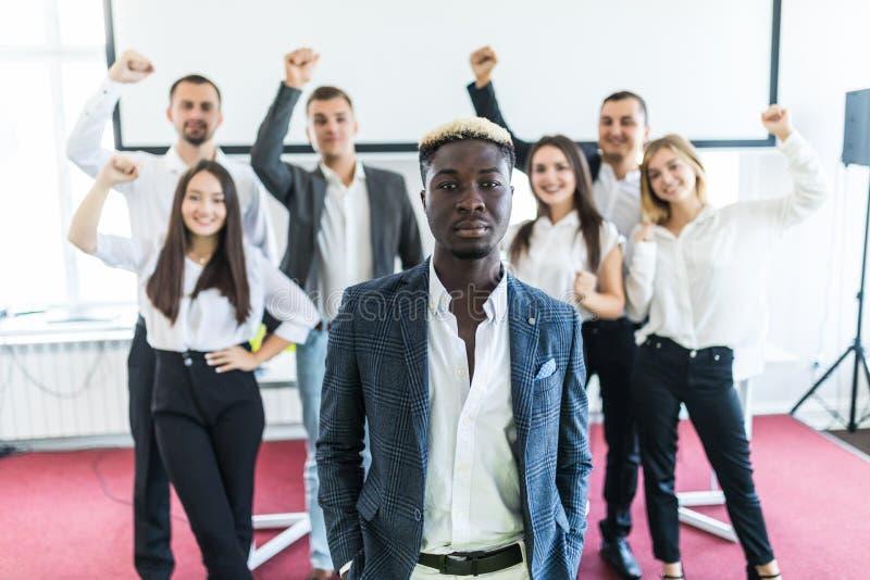 Stilig afrikansk affärsman framme av gruppen av att fira businesspeople på bakgrund royaltyfria foton