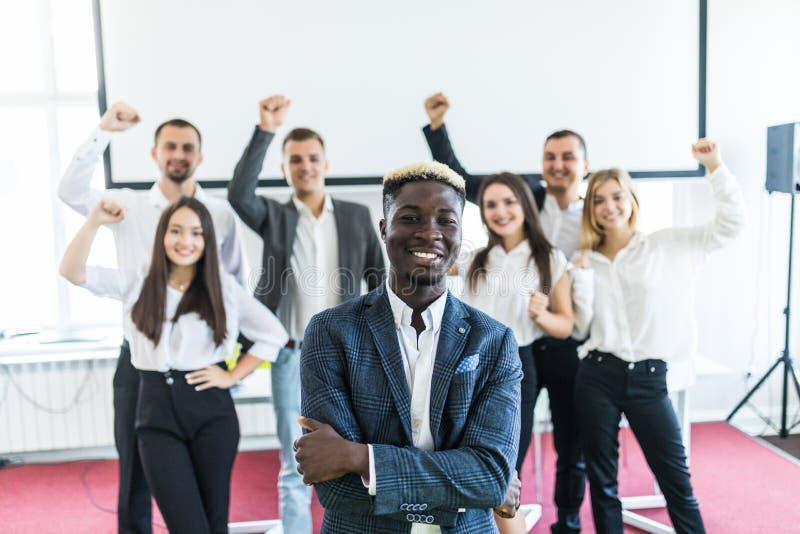 Stilig afrikansk affärsman framme av gruppen av att fira businesspeople på bakgrund royaltyfri fotografi