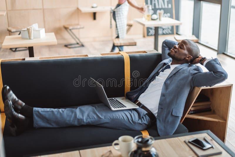 stilig afrikansk amerikanaffärsman med bärbara datorn som kopplar av på soffan arkivbilder