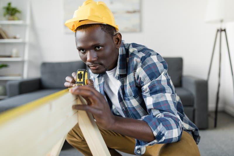 stilig afrikansk amerikanbyggmästare med att mäta royaltyfri foto