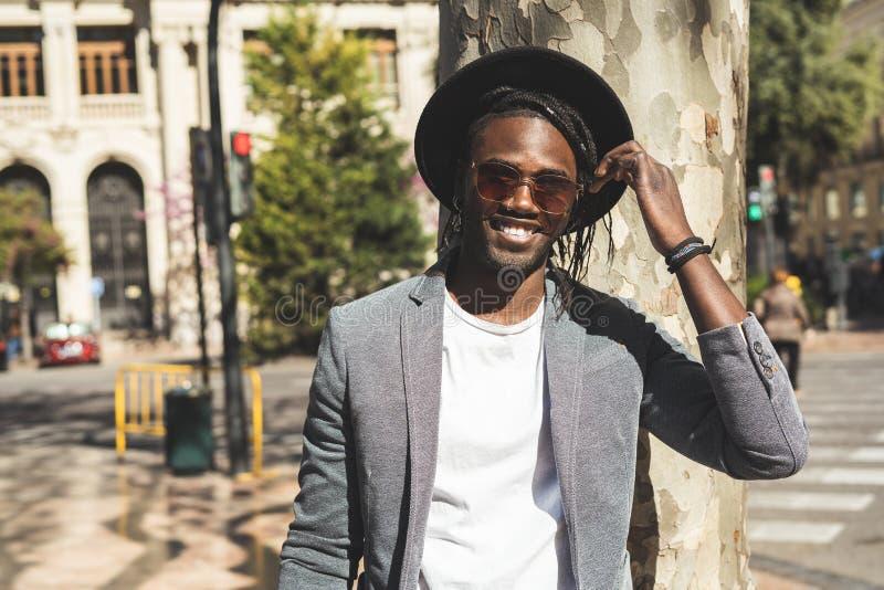 Stilig afrikansk amerikangrabbstående som ler med stil på gatan arkivbilder
