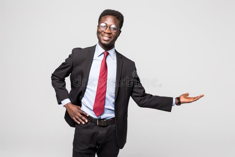 Stilig afrikansk amerikanman i en svart affärsdräkt som gör en gest som om att visa en produktprövkopia på grå färger fotografering för bildbyråer