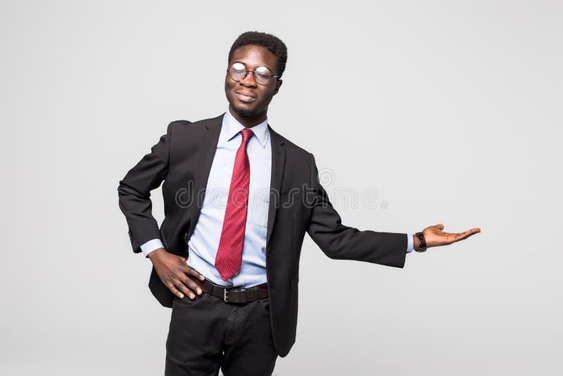 Stilig afrikansk amerikanman i en svart affärsdräkt som gör en gest som om att visa en produktprövkopia på grå färger royaltyfria bilder