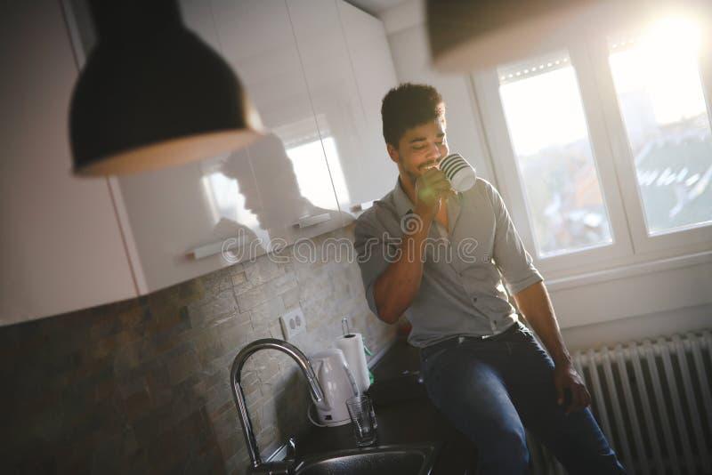 Stilig afrikansk amerikanman som dricker kaffe i kök fotografering för bildbyråer